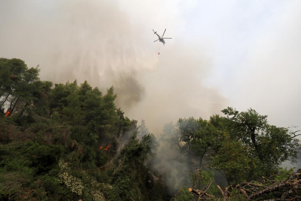 An helicopter drops water during a wildfire near Kechries village on the island of Evia, about 144 kilometers (90 miles) north of Athens, Greece, Thursday, Aug. 5, 2021. Forest fires fueled by a protracted heat wave raged overnight and into Thursday in Greece, threatening the archaeological site at the birthplace of the modern Olympics and forcing the evacuation of dozens of villages. (AP Photo/Thodoris Nikolaou)