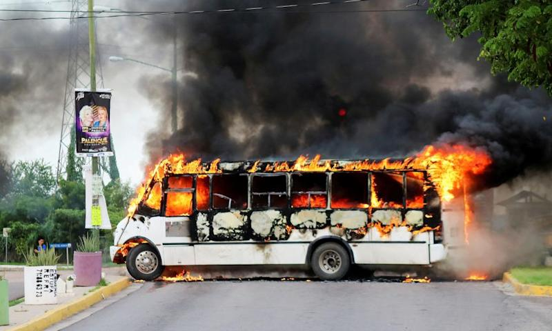 A bus was set alight by cartel gunmen to block a road during clashes with federal forces in Culiacán.