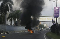Burning barricades set by protesters against police brutality in Lagos, Nigeria, Wednesday Oct. 21, 2020. After 13 days of protests against alleged police brutality, authorities have imposed a 24-hour curfew in Lagos, Nigeria's largest city, as moves are made to stop growing violence. (AP Photo/Sunday Alamba)
