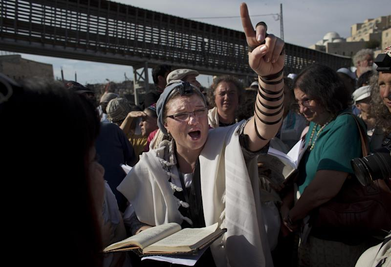 """A Jewish women from the """"Women of the Wall"""" organization, leads a prayer, at the Western Wall, the holiest site where Jews can pray in Jerusalem's old city, Friday, May 10, 2013. The """"Women of the Wall"""" group has been holding monthly prayer services on the first day of the Hebrew month at the Western Wall in Jerusalem for more than two decades, wearing prayer shawls and performing religious rituals reserved for men under Orthodox Judaism. Accused by ultra-Orthodox leaders of violating """"local custom"""" at the holy site, many members have been arrested. On Friday the tables were turned because of the court ruling. Police protected the women and arrested three ultra-Orthodox men for disorderly conduct, police spokesman Micky Rosenfeld said. (AP Photo/Bernat Armangue)"""