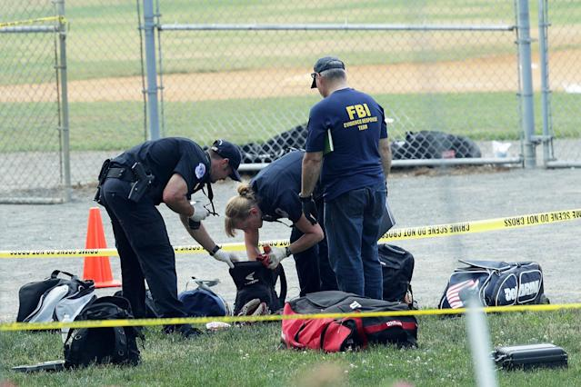 <p>Investigators search the bags that have been left behind at the Eugene Simpson Stadium Park where a shooting had happened June 14, 2017 in Alexandria, Va. (Photo: Alex Wong/Getty Images) </p>