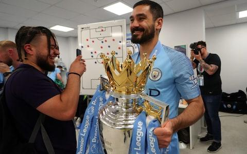 Ilkay Gundogan of Manchester City celebrates with the Premier League Trophy after winning the title following the Premier League match between Brighton & Hove Albion and Manchester City - Credit: GETTY IMAGES