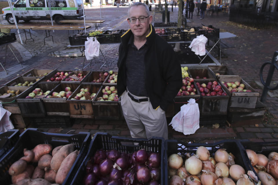 John Gold, self-employed graphics designer, poses at a farmer's market outside his office in Portland, Maine, Wednesday, Oct. 23, 2019. Gold has been covered by the Affordable Care Act since it started, plans on shopping for plans for 2020 again when the enrollment season starts Nov. 1. The 2020 sign-up season for the Affordable Care Act is getting underway with premiums down slightly in many states and more health plan choices for consumers. (AP Photo/Charles Krupa)