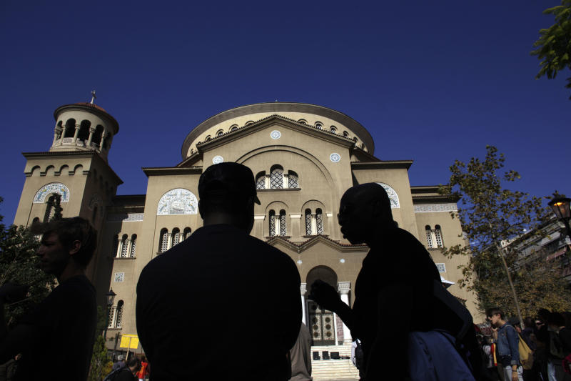 African immigrants chat in front of the Orthodox church of Saint Panteleimon during an anti-racist protest in Athens on Saturday, Oct. 26, 2013. Some 2000 protesters took part in a protest opposing a rally which was due to be held by the extreme-right Golden Dawn party. (AP Photo/Kostas Tsironis)