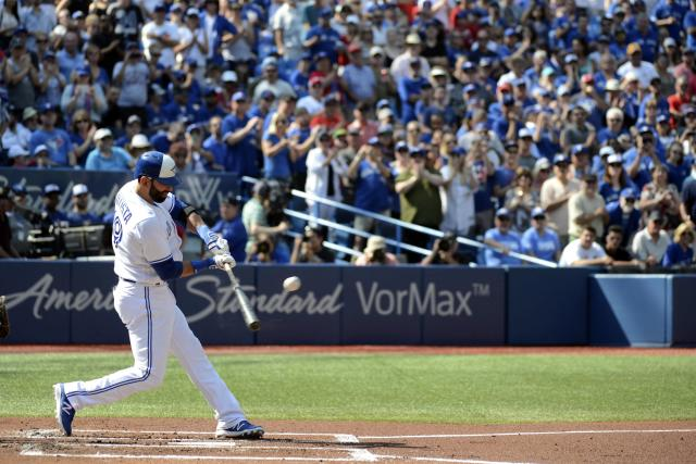 Toronto Blue Jays' Jose Bautista hits a single in front of a crowd on their feet cheering him. (Jon Blacker/AP)
