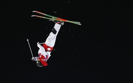 Canada's Alex Bilodeau performs jump during men's freestyle skiing moguls finals at 2014 Sochi Winter Olympic Games in Rosa Khutor