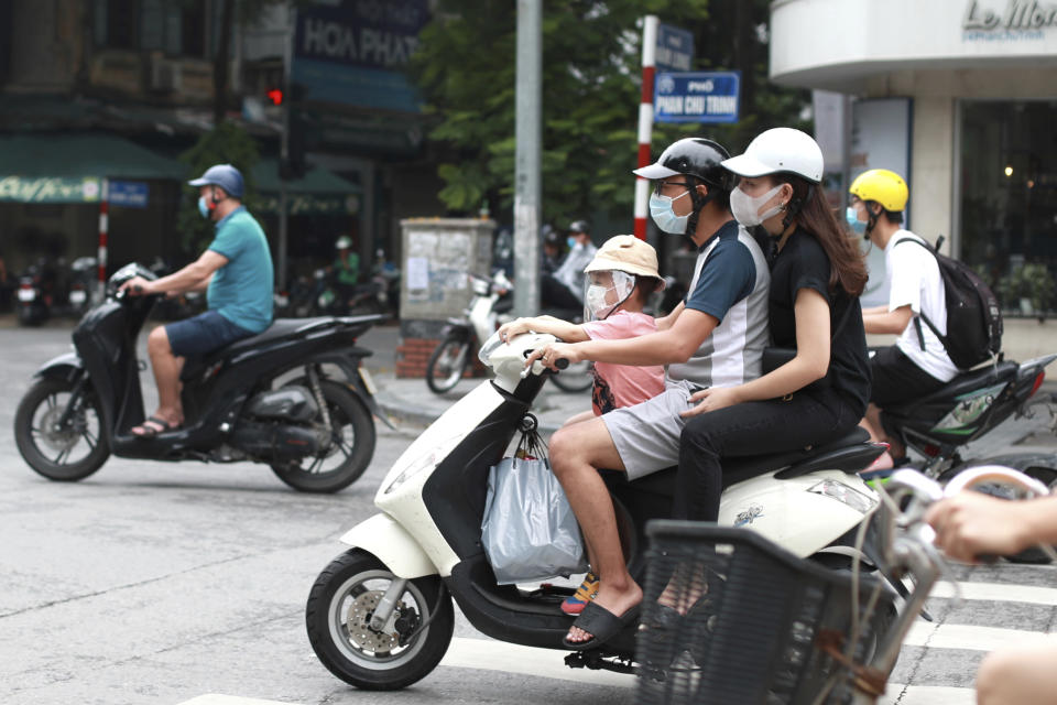 People wearing face masks ride motorcycles in Hanoi, Vietnam, Monday, Aug. 3, 2020. Vietnam has tightened travel and social restrictions after the country's death toll of COVID-19 to six. (AP Photo/Hau Dinh)