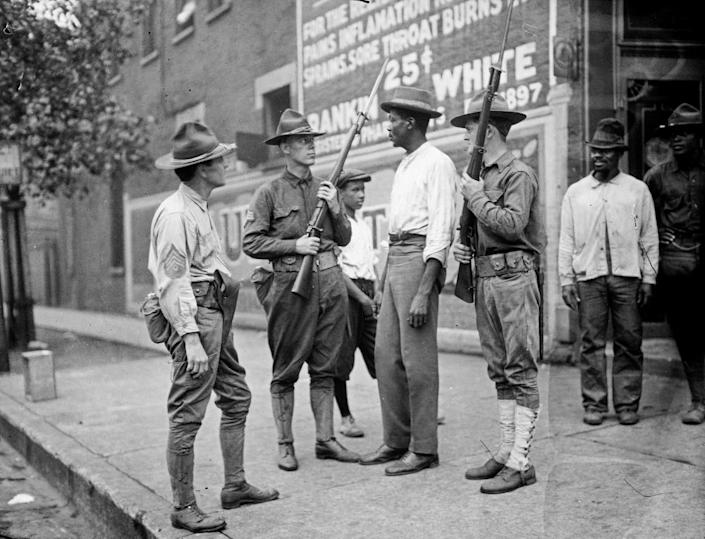 "<span class=""element-image__caption"">In this 1919 photo provided by the Chicago History Museum, armed national guard and African American men stand on a sidewalk during race riots in Chicago.</span> <span class=""element-image__credit"">Photograph: Chicago History Museum/AP</span>"