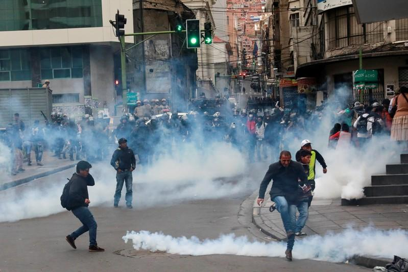 People react amid tear gas during clashes between members of the security forces and supporters of former Bolivian President Evo Morales in La Paz