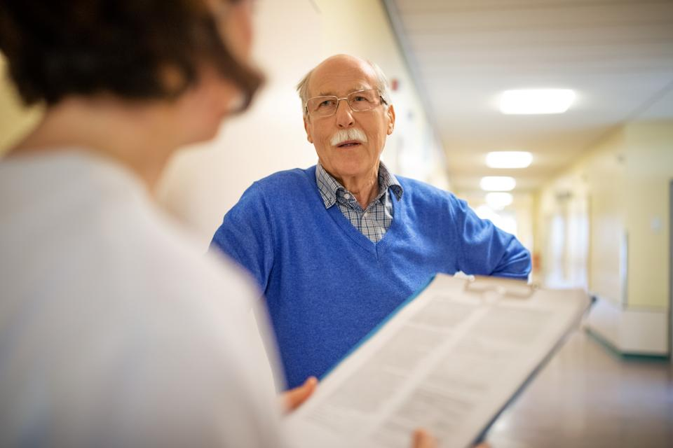Senior man talking with doctor in hospital hallway. Elderly patient discussing with female physician in nursing home.