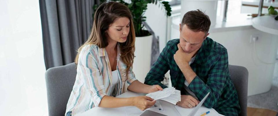 Husband and wife preparing bills to pay sitting at kitchen table.