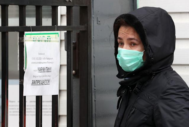 A woman is pictured wearing a mask next to a quarantine notice outside a hospital in Minsk, Belarus, on 28 February. (Getty Images)