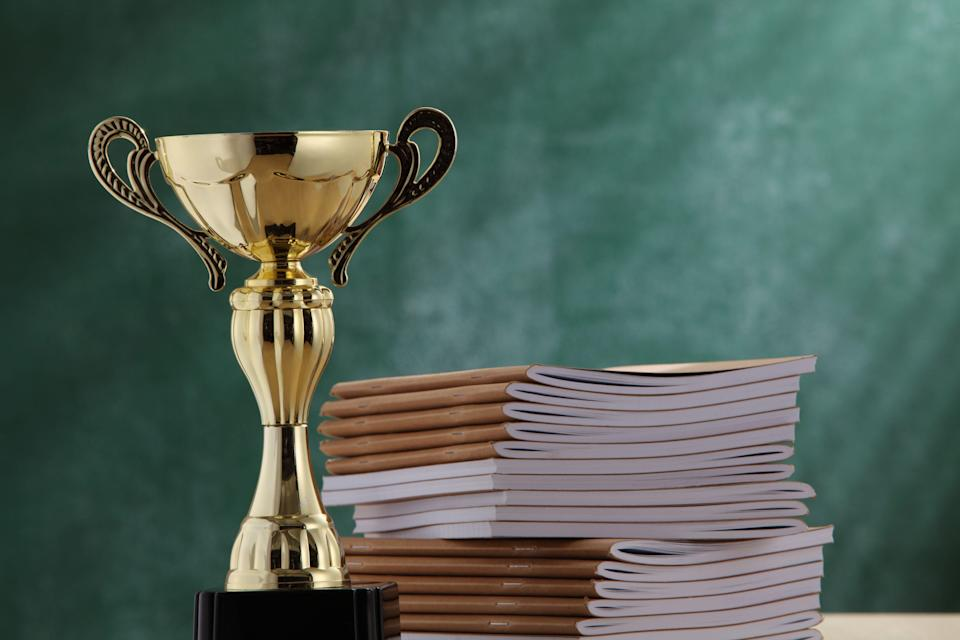 Close-Up Of Trophy By Books