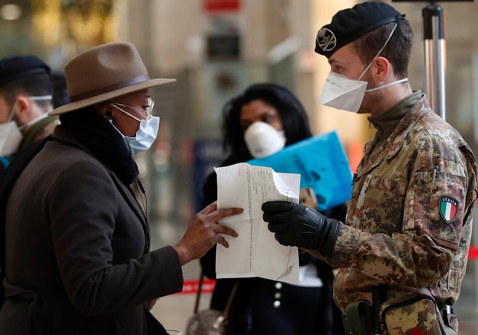 Police officers and soldiers check passengers leaving from Milan main train station, Italy, Monday, March 9, 2020. Italy took a page from China's playbook Sunday, attempting to lock down 16 million people — more than a quarter of its population — for nearly a month to halt the relentless march of the new coronavirus across Europe. Italian Premier Giuseppe Conte signed a quarantine decree early Sunday for the country's prosperous north. Areas under lockdown include Milan, Italy's financial hub and the main city in Lombardy, and Venice, the main city in the neighboring Veneto region. (AP Photo/Antonio Calanni)