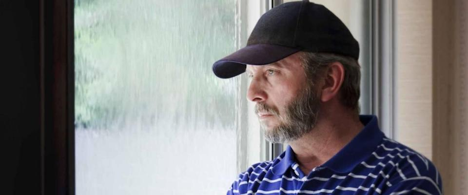 An adult man looking out of a rain-covered window could illustrate recent job loss, unemployment, quarantine, financial or health problems or staying home safe from coronavirus