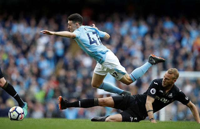"Soccer Football - Premier League - Manchester City v Swansea City - Etihad Stadium, Manchester, Britain - April 22, 2018 Manchester City's Phil Foden is fouled by Swansea City's Mike van der Hoorn REUTERS/Phil Noble EDITORIAL USE ONLY. No use with unauthorized audio, video, data, fixture lists, club/league logos or ""live"" services. Online in-match use limited to 75 images, no video emulation. No use in betting, games or single club/league/player publications. Please contact your account representative for further details."