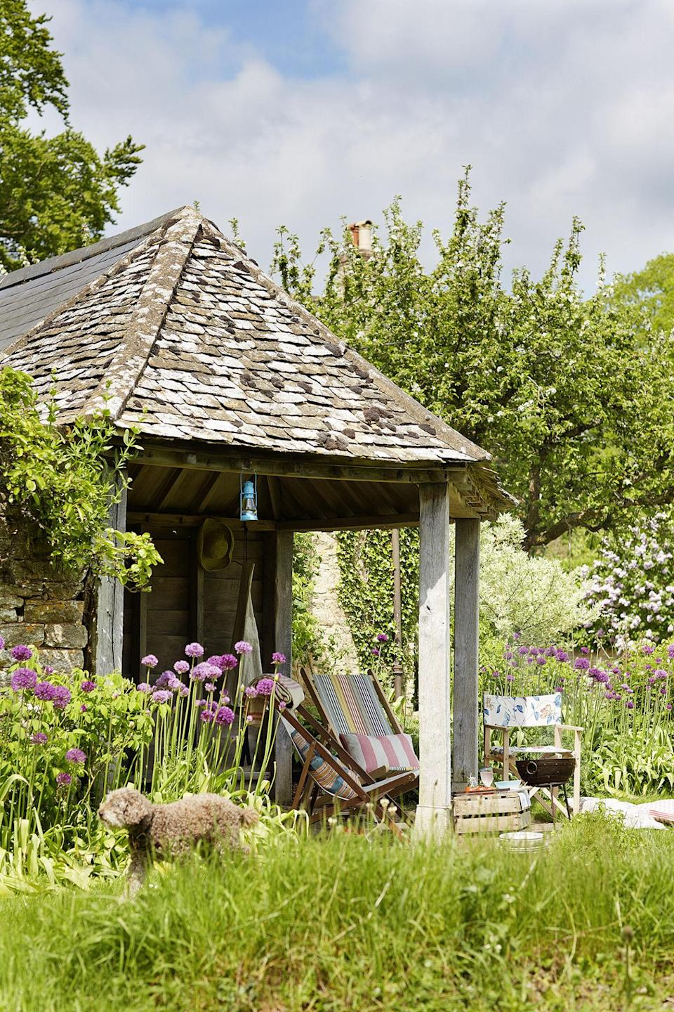 <p>A bespoke open-sided garden building made of green-oak timber and reclaimed limestone provides an ideal place to admire the garden.</p>