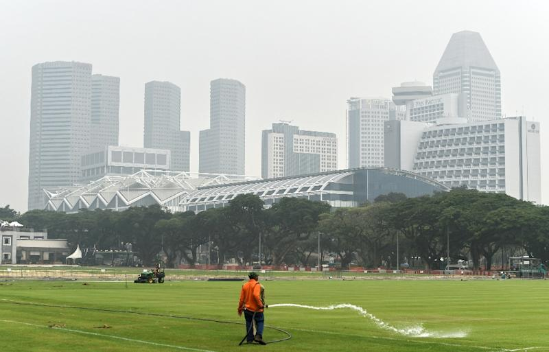 A worker waters a field as downtown buildings are shrouded in smog in Singapore on October 5, 2015