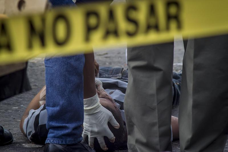 A forensic workers checks the body of a victim of a shootout between private security guards and gang members, at the central market in San Salvador, El Salvador, Wednesday, March 15, 2017. At least 30 people, mostly gang members, died in the last 24 hours in El Salvador on one of the most violent days so far this year. (AP Photo/Salvador Melendez)