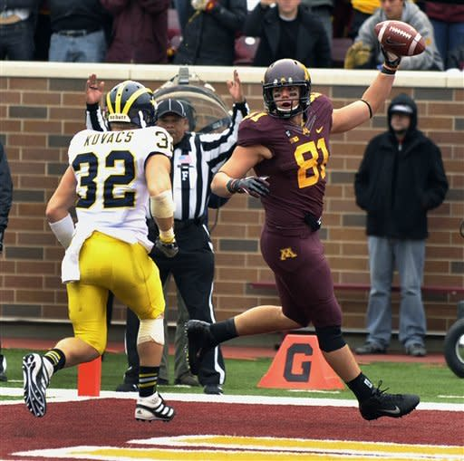 Minnesota John Rabe, right, walks into the end zone for a touchdown as Michigan Lamonte Edwards, left, attempts to defend during the first quarter of an NCAA college football game, Saturday, Nov. 3, 2012, in Minneapolis. (AP Photo/Tom Olmscheid)