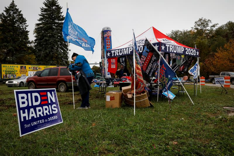 A vendor sells merchandise to supporters of U.S. President Trump next to a campaign sign for Democratic U.S. presidential nominee and former Vice President Biden near a campaign event in Erie