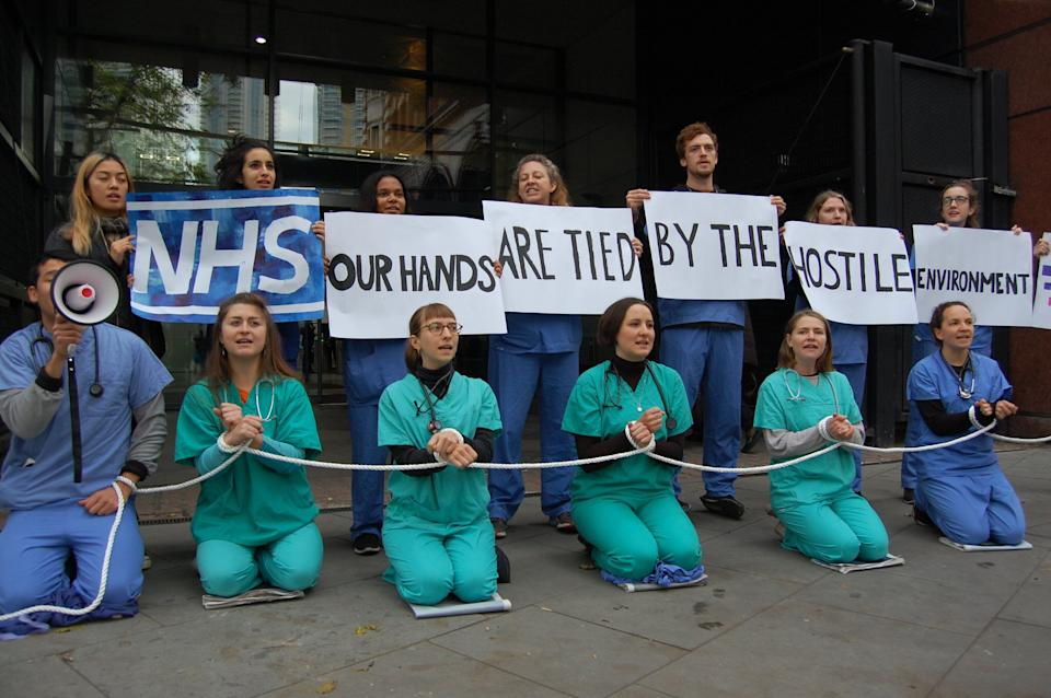 Medical staff protesting against the NHS' upfront charging policies, introduced as part of the hostile environment in 2017.  (Photo: Medact )