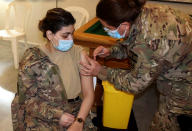 In this photo released by the Lebanese Army official website, a Lebanese Army soldier, receives a Sinopharm COVID-19 vaccine, at one of the military vaccination centers, in Beirut, Lebanon, Thursday, April 8, 2021. The Lebanese army said thousands of soldiers will be vaccinated in the coming weeks. Lebanon received a gift of 90,000 Sinopharm shots from China last week of which some of them will be used to inoculate members of the military. (Lebanese Army Website via AP)