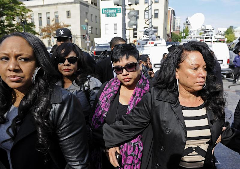 Singer Chris Brown's mother, Joyce Hawkins, right, is escorted into a courthouse in Washington, Monday, Oct. 28, 2013, for her son's arraignment on a felony assault charge. Brown is accused of punching a man in the face after the man said he tried to get into a photo with the singer outside a hotel, according to police, the latest legal trouble for the Grammy Award-winning artist. (AP Photo/Cliff Owen)