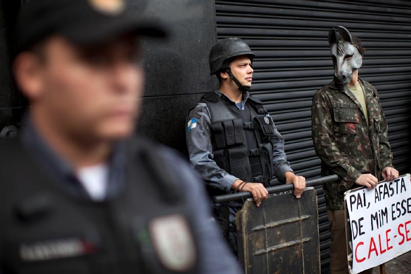 "An activist wearing a donkey mask stands next to police as they stand guard outside a military club during a protest in downtown Rio de Janeiro, Brazil, Thursday March 29, 2012. A club of retired military officers held its annual celebration of Brazil's 1964 military coup as usual, but faced protestors as members arrived for the event. Unlike its Latin American neighbors, Brazil never had a formal investigation into its 20-year dictatorship. The sign reads in Portuguese "" Father keep that one away…shut-up,"" a play on words from a song by famous singer Chico Buarque which was censored during the dictatorship. (AP Photo/Felipe Dana)"