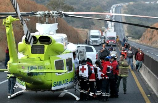 Firefighters and forensic medical personnel carry an injured person into a helicopter after a tourist van and a cargo truck collided on the Lagos de Moreno highway in Zapotlanejo, Jalisco State, Mexico