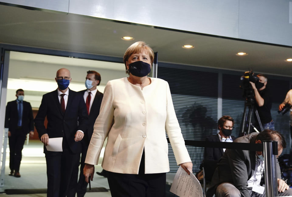 German Chancellor Angela Merkel, foreground arrives for a coronavirus press conference, in Berlin, Tuesday, Sept. 29, 2020. Chancellor Angela Merkel and the governors of Germany's 16 states conferred on how to prevent the country's coronavirus infection figures from accelerating to the levels being seen in other European countries. (Kay Nietfeld/dpa via AP)