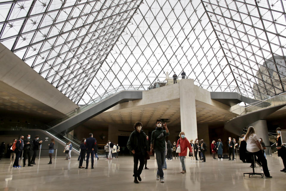 People stroll inside the Louvre museum, Wednesday, May, 19, 2021 in Paris. Museums must restrict entries so there is 8 square meters of space (86 square feet) per visitor. Café and restaurant terraces are reopening Wednesday after a shutdown of more than six months deprived people of what feels like the essence of life — sipping coffee and wine with friends outdoors — to save lives during the coronavirus pandemic. (AP Photo/Thibault Camus)