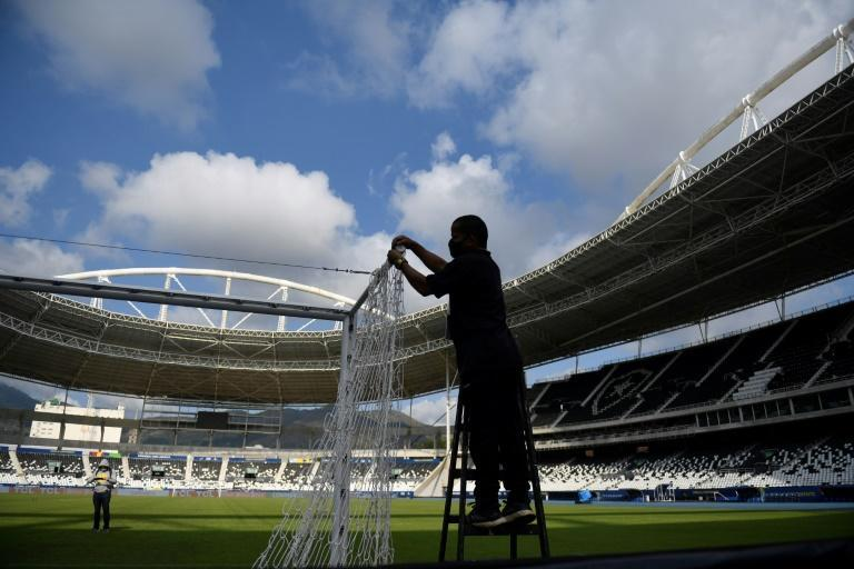 An employee installs the goal net at one end of the Nilton Santos Olympic stadium in Rio de Janeiro ahead of a Copa America match June 16, 2021