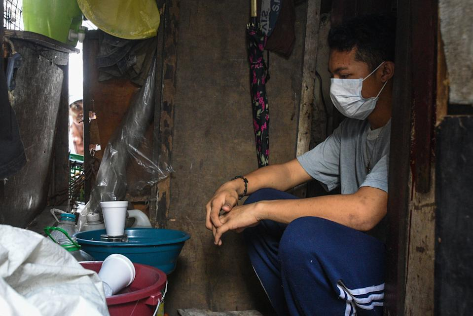 This photo taken on March 18, 2020 shows a man wears a face mask as a preventive measure against the spread of the COVID-19 coronavirius in Manila. - Asian nations have imposed increasingly heavy measures to fight the outbreak of the COVID-19 coronavirus, the Philippines has ordered half its population of some 110 million to stay home. (Photo by Maria TAN / AFP) / TO GO WITH Health-virus-Philippines-poverty,FOCUS by Joshua Melvin and Ron Lopez (Photo by MARIA TAN/AFP via Getty Images)