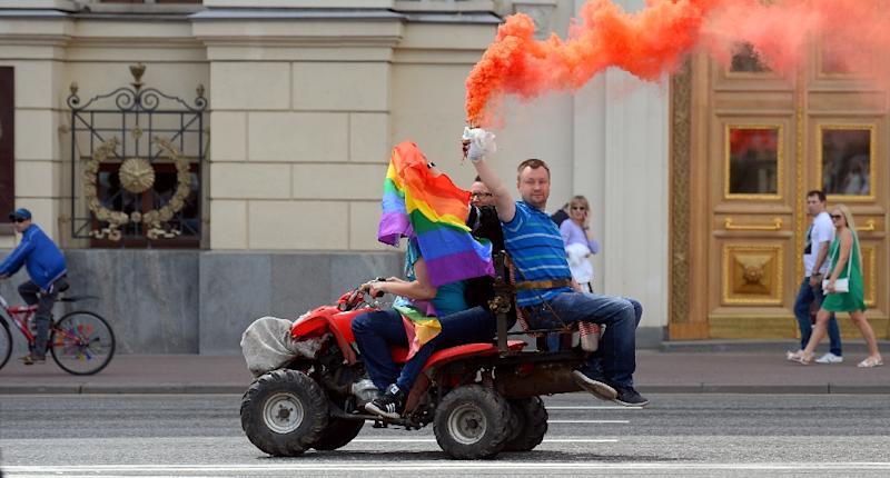 Gay and LGBT rights activist Nikolai Alexeyev (R) holds a flare as he rides a quad-bike during an unauthorized gay rights activists rally in central Moscow on May 30, 2015 (AFP Photo/Dmitry Serebryakov)
