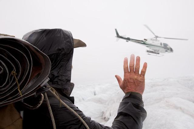 Triumvirate Glacier, Alaska: Marty Raney waves at a helicopter with one of the groups leaving the LZ.