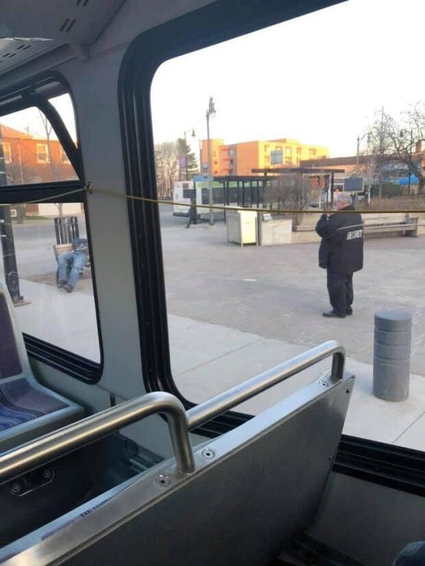 Photos shared on social media Thursday evening show a security worker at city hall taking photos and laughing at two men sleeping on a bench in Thunder Bay, Ont. (Submitted by Tatjana Shawanamash-Ignace - image credit)