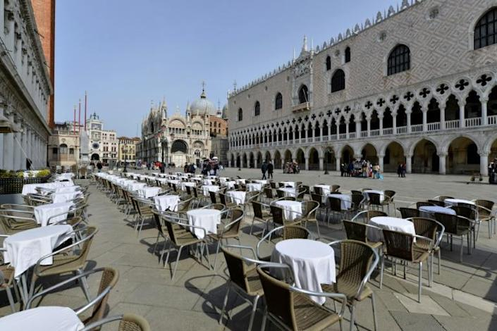 Deserted tables in front of the Doge palace in Venice, Italy (AFP Photo/ANDREA PATTARO)