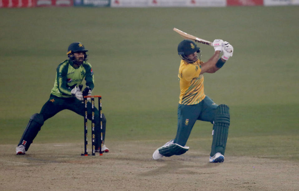 South Africa's Reeza Hendricks, right, follows the ball after playing a shot for six while Pakistan's Mohammad Rizwan watches during the 2nd Twenty20 cricket match between Pakistan and South Africa at the Gaddafi Stadium, in Lahore, Pakistan, Saturday, Feb. 13, 2021. (AP Photo/K.M. Chaudary)