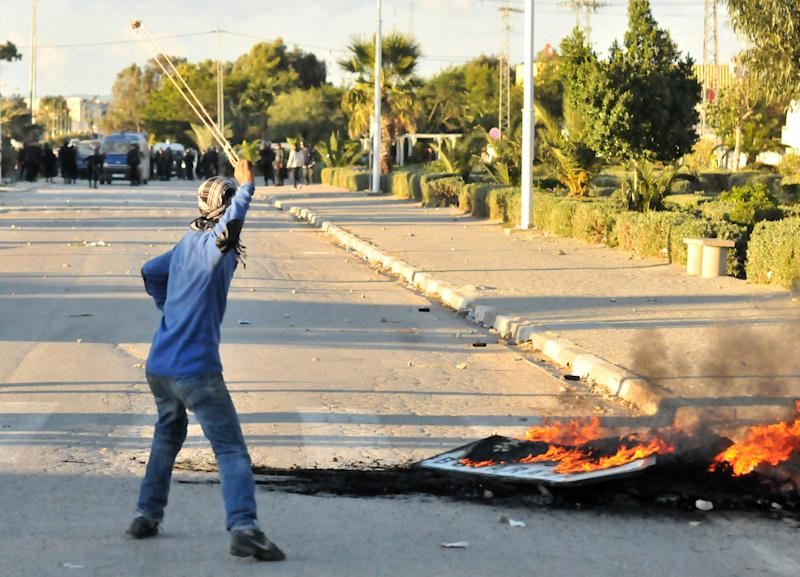 A demonstrator uses a slingshot against government forces in Siliana, northern Tunisia, Thursday, Nov.29, 2012. Tunisia's army intervened in a third day of violent clashes in a northern town between police and striking residents who are demanding jobs and investment. After two days of battles that a hospital said left more than 300 people injured, police pulled out of Siliana Wednesday night. Witnesses said 15,000 people marched through the town Thursday demanding the governor's resignation. (AP Photo)