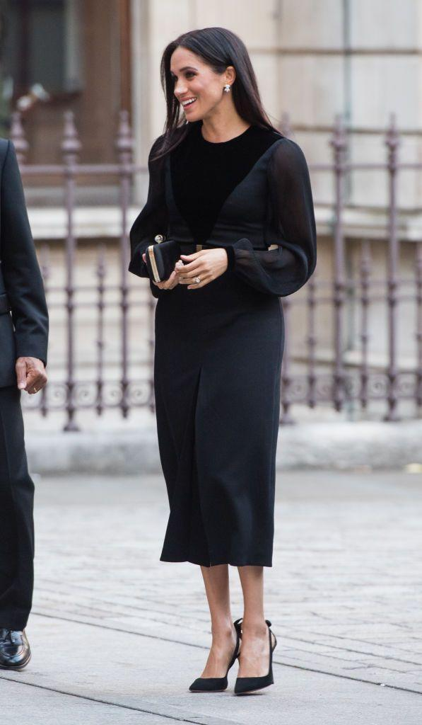 """<p><a href=""""https://www.townandcountrymag.com/style/fashion-trends/a23453834/meghan-markle-first-solo-event-oceania-exhibit-black-dress-givenchy/"""" rel=""""nofollow noopener"""" target=""""_blank"""" data-ylk=""""slk:Meghan Markle wore a sleek black Givenchy dress"""" class=""""link rapid-noclick-resp"""">Meghan Markle wore a sleek black Givenchy dress</a> for her very first solo appearance at the Royal Academy of Arts in London. The Duchess accessorized with a Givenchy clutch and a pair of heels by Aquazzura.</p>"""