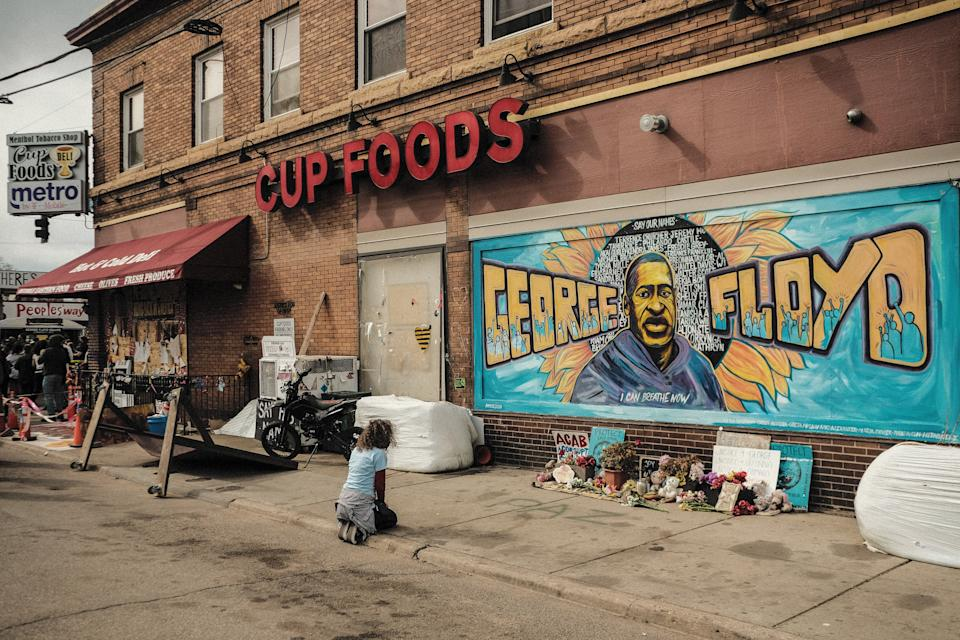 A woman pays respect to a mural of George Floyd by the Cup Foods where he was killed by Minneapolis police officer Derek Chauvin in Minneapolis. (Photo: SOPA Images via Getty Images)