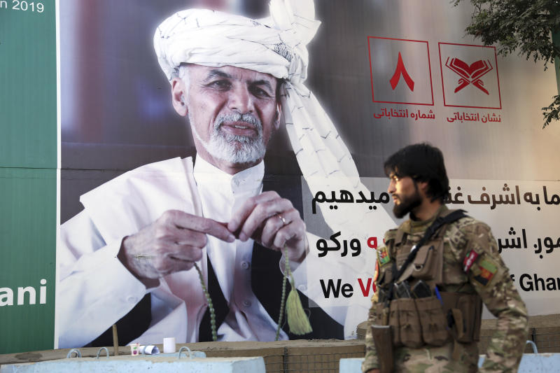 In this Monday, Sept. 23, 2019 photo, an Afghan soldier stands guard in front of an election poster for presidential candidate Ashraf Ghani in Kabul, Afghanistan. The Taliban have warned Afghanistan's 9.6 million eligible voters to stay away from polling stations during Saturday's presidential election. Ghani and and Chief Executive Abdullah Abdullah -- who shared power for five years in a so-called unity government -- are the leading contenders in the election. (AP Photo/Rahmat Gul)