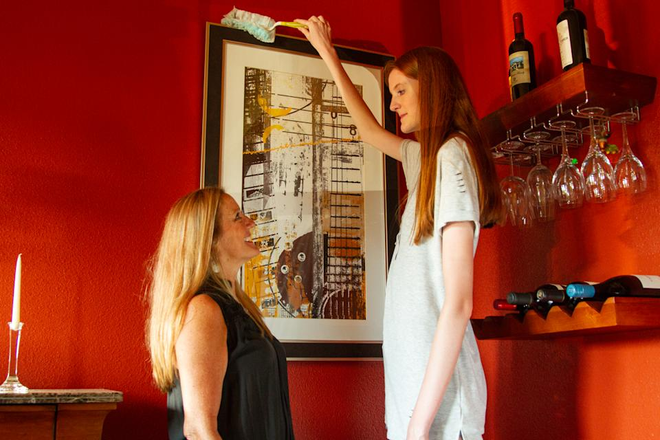 ***EXCLUSIVE VIDEO AVAILABLE*** AUSTIN, TX, USA - 11 AUGUST 2019: 16-year-old Maci Currin, whose 53 inch long legs are believed to be the world's longest, towers over her mother Trish as she dusts the top of a painting on 11 August, 2019, in Austin, Texas. A TOWERING teenager from Texas is about to strut her way into the record books as the proud owner of the world's longest legs. Aged only 16, Maci Currin, from Austin, Texas, has legs measuring an incredible 53 inches - smashing the previous record of 52.2 inches held by Ekaterina Lisina, of Russia. The 6ft 9in aspiring model was only 19 inches when born, but a series of growth spurts meant she rocketed to 5ft 7in by the time she was nine years old. Maci also has an inseam of 43 inches and has to stoop to avoid banging her head when walking through doors, but says she is proud of her lengthy limbs despite the added attention they bring. PHOTOGRAPH BY: Bradley Beesley / Barcroft Media (Photo credit should read Bradley Beesley / Barcroft Media / Barcroft Media via Getty Images)