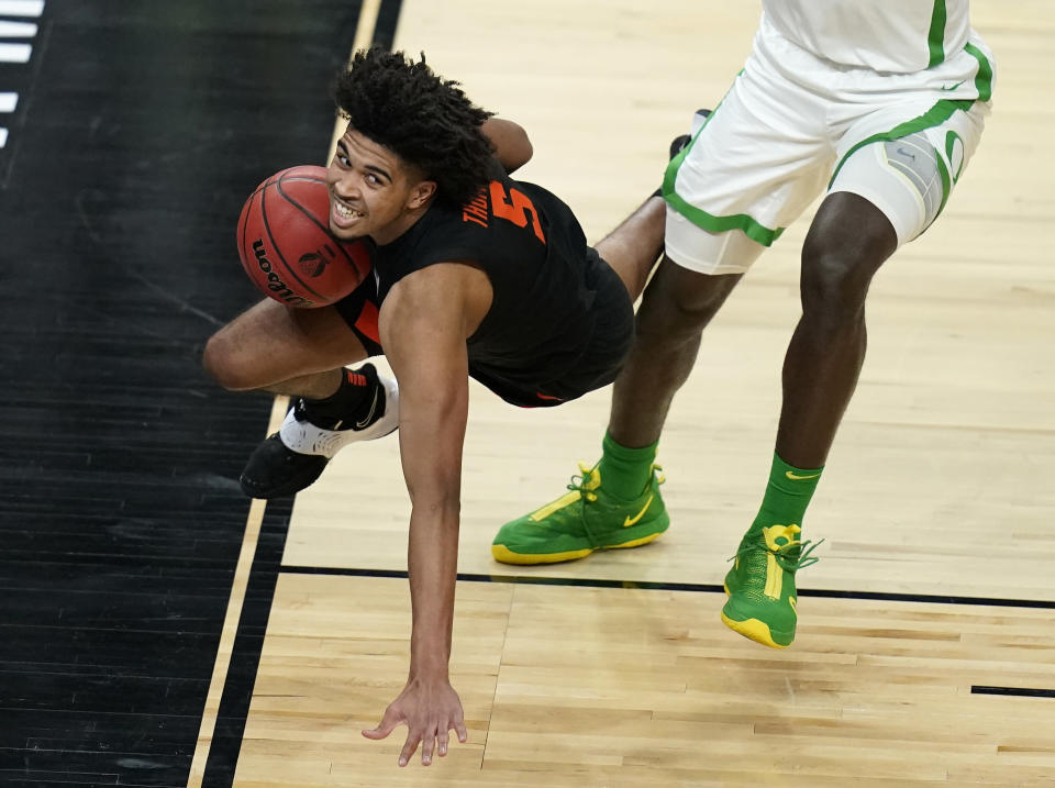 Oregon's Franck Kepnang, right, fouls Oregon State's Ethan Thompson (5) during the first half of an NCAA college basketball game in the semifinal round of the Pac-12 men's tournament Friday, March 12, 2021, in Las Vegas. (AP Photo/John Locher)