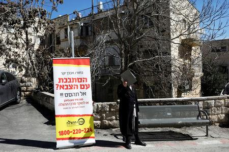 An Ultra-Orthodox Jewish man covers his face as he stands near a banner, in front of the Israeli military recruiting office in Jerusalem, March 13, 2018. REUTERS/Ronen Zvulun
