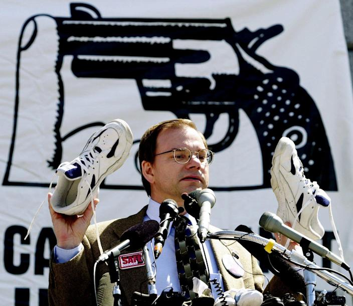 Tom Mauser holds up a pair of shoes belonging to his late son, Daniel, who was killed in the Columbine shooting, during a rally at the capitol in Denver, April 11, 2000. Mauser placed the shoes with over 4,000 other pairs, representing children killed by handguns in one year. (Photo: Ed Andrieski/AP)