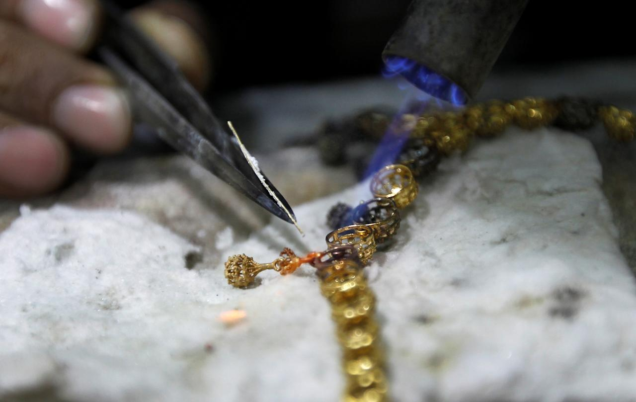 A goldsmith works on a necklace at his workshop in Rawalpindi, Pakistan December 12,  2017. REUTERS/Caren Firouz