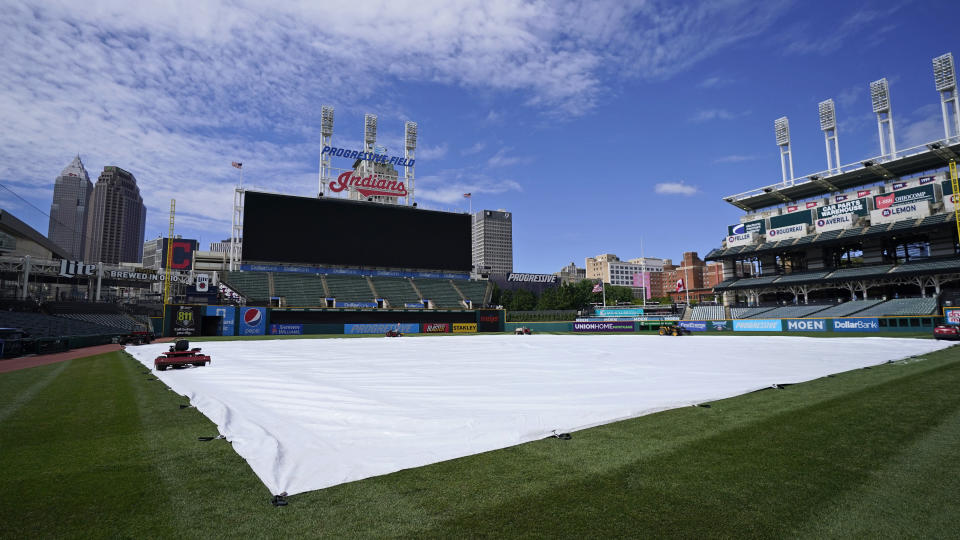 The tarp rests on the field after a baseball game between the Toronto Blue Jays and the Cleveland Indians was postponed due to inclement weather, Saturday, May 29, 2021, in Cleveland. The game will be rescheduled as a traditional doubleheader Sunday. (AP Photo/Tony Dejak)