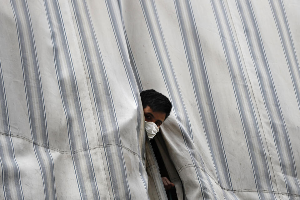 In this Saturday, May 23, 2020 photo, a Bangladeshi worker looks from behind a curtain of his apartment balcony in a building where dozens of foreign workers living in overcrowded apartments have tested positive with the coronavirus, in Beirut, Lebanon. Some 250,000 registered migrant laborers in Lebanon — maids, garbage collectors, farm hands and construction workers — are growing more desperate as a crippling economic and financial crisis sets in, coupled with coronavirus restrictions. With no functioning airports and exorbitant costs of repatriation flights, many are trapped, unable to go home. (AP Photo/Hussein Malla)